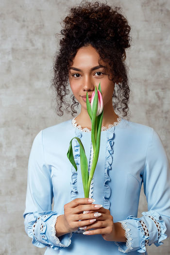 Portrait of beautiful woman holding tulip while standing against wall