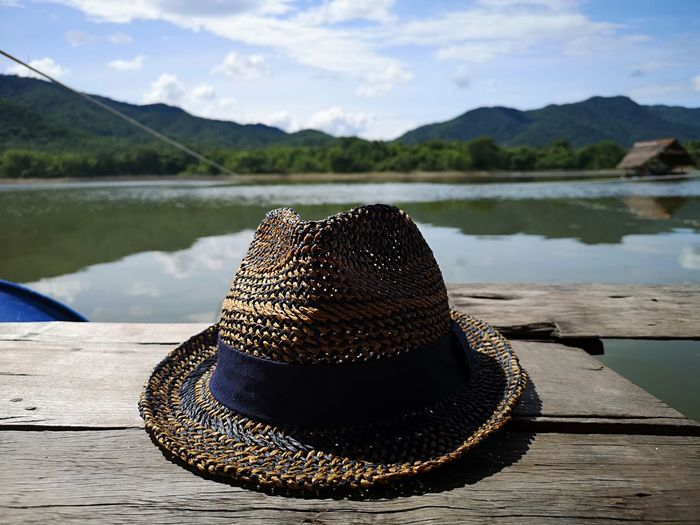 Close-up of hat on pier against lake