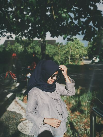 Woman wearing hijab and sunglasses while standing at public park