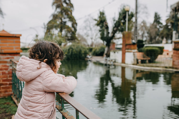 Girl standing by railing and lake