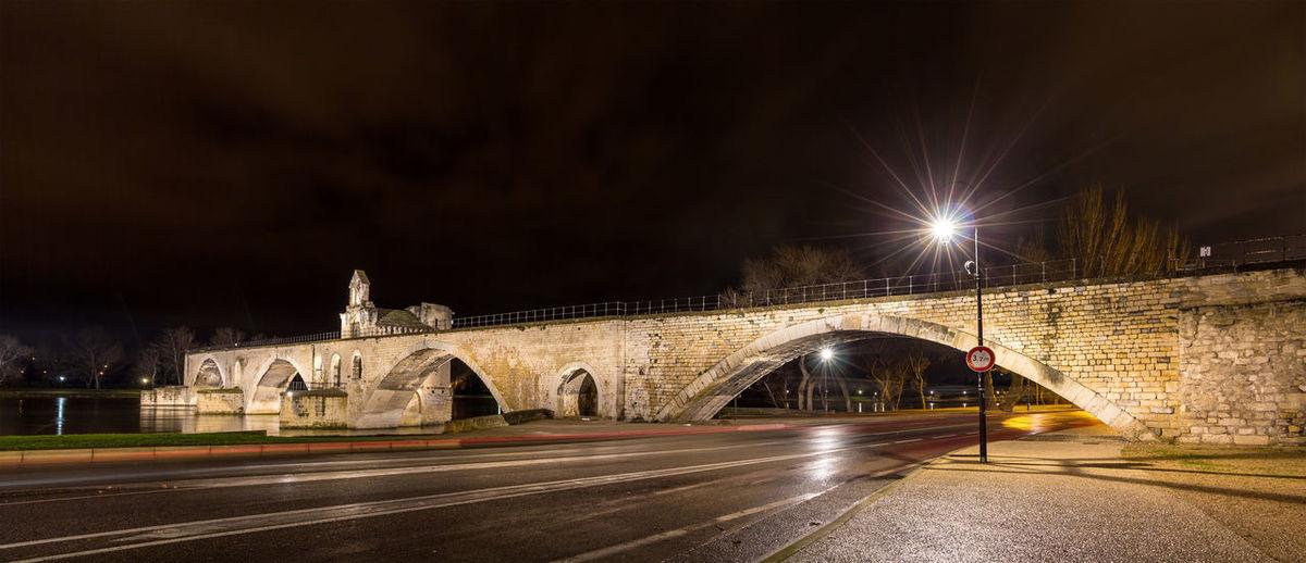 Bridge over illuminated street at night