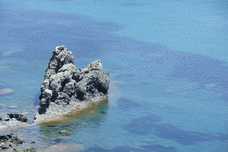 High Angle View Of Rock In Sea Against Sky