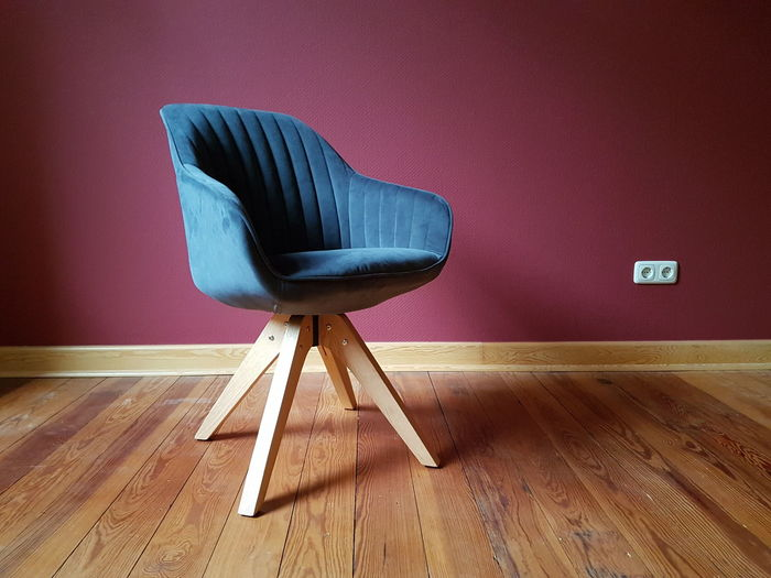Empty chair on hardwood floor at home