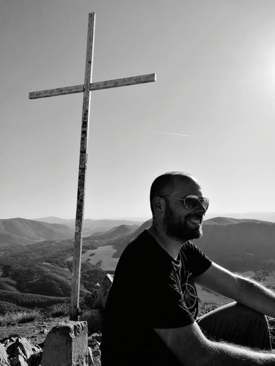 Smiling Man By Cross Looking Away Against Mountain And Sky