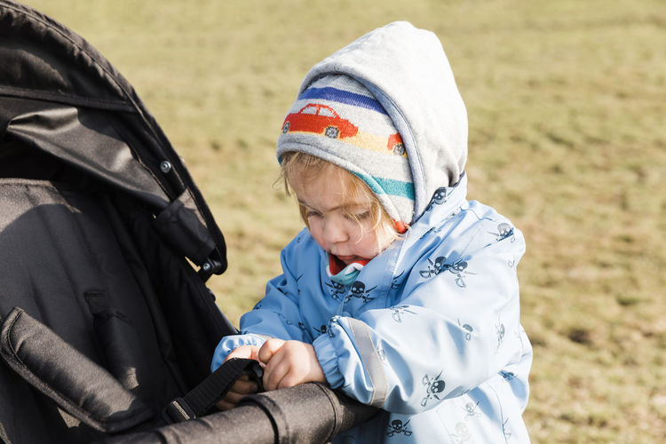Cute Girl Playing With Baby Stroller On Field
