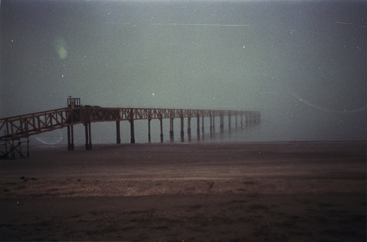 PIER OVER SEA AGAINST SKY AT NIGHT