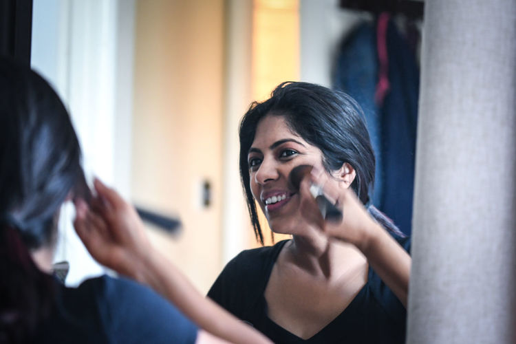Reflection of smiling woman applying blusher on face in mirror at home