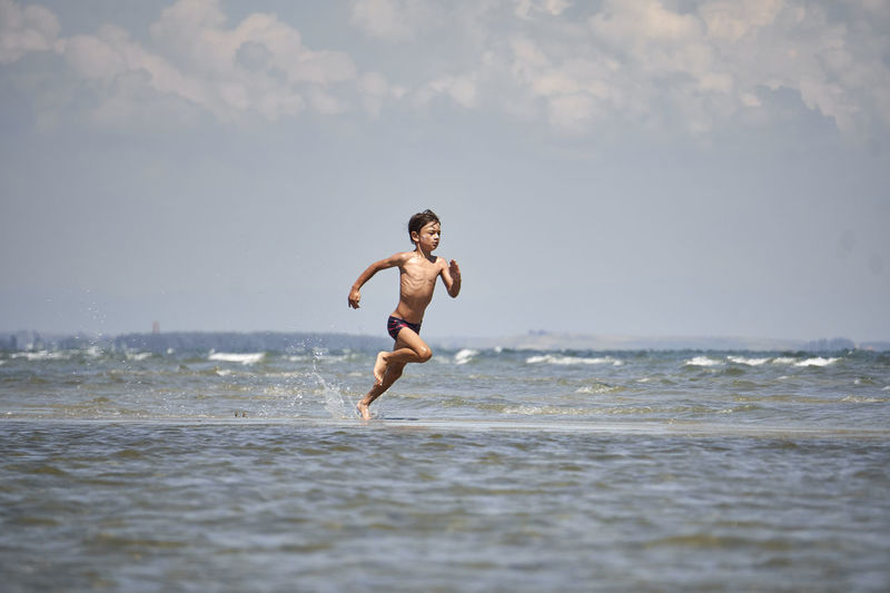 Full length of shirtless boy running on sea against sky