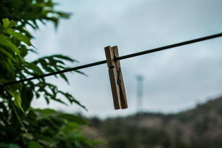 Low angle view of clothespins on rope against sky