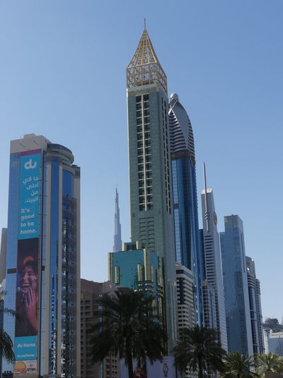 Skyscrapers on Sheik Zayed Road & Burj Khalifa in background, Dubai, United Arab Emirates 2019 Dubai UAE 2019 Sheik Zayed Road Tall - High Blue Sky Low Angle View City No People Burj Khalifa Skyscrapers Modern Design Modern Architecture Tower Blocks Palm Trees Sunlight And Shade Glass And Steel Structures Architecture Building Exteriors Building Facades Composition Full Frame Outdoor Photography Modern Tourist Destination