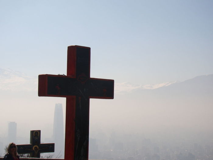View of cross in city against sky