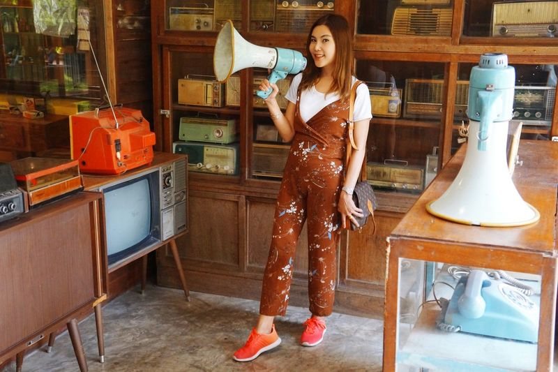 Young woman holding megaphone while standing in antique store