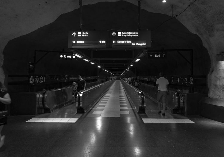 public transportation in Stockholm Illuminated Architecture Indoors  Transportation The Way Forward Direction Real People Sign Built Structure Lighting Equipment Group Of People Public Transportation Travel Information Communication Information Sign Diminishing Perspective Text Mode Of Transportation Light Modern Moving Walkway  Ceiling Streetphotography Streetphoto_bw Urban Photography Exceptional Photographs Blackandwhite Monochrome City Life Underground