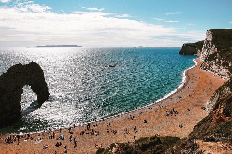 EyeEm Selects Durdle Door Sea Beach Sand Nature Water Scenics Beauty In Nature Horizon Over Water Tranquility Sky Day Cloud - Sky Outdoors Travel Destinations Vacations Cliff Wave Large Group Of People People