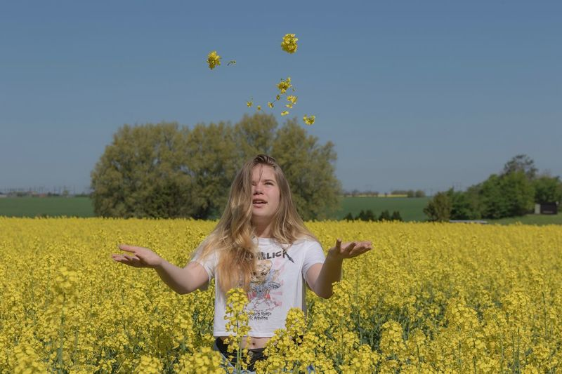 Teenage Girl Playing With Flowers While Standing In Farm Against Blue Sky