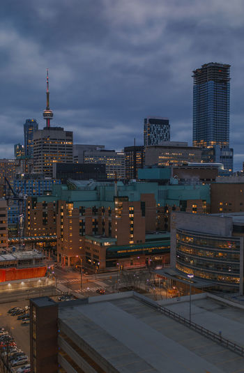 Modern buildings against cloudy sky in city at dusk