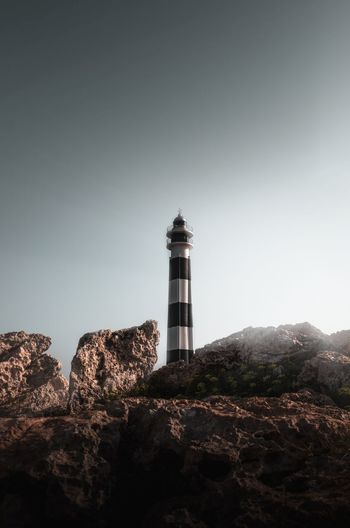 Lighthouse on rock by building against clear sky