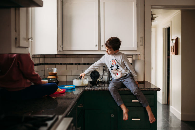 Rear view of boy sitting at home