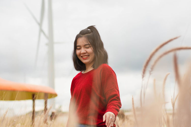 Happy Young Woman Standing On Field
