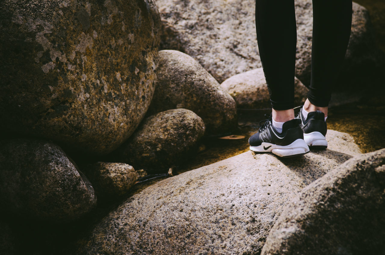 low section, human leg, rock - object, real people, shoe, one person, day, lifestyles, outdoors, human body part, standing, men, nature, close-up