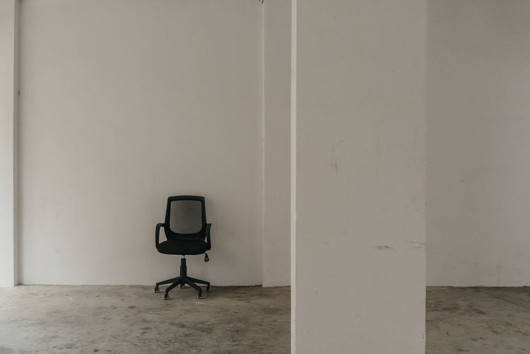 Empty Chair Against White Wall In Room