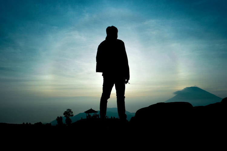 Silhouette Of Person Standing On Landscape At Sunset