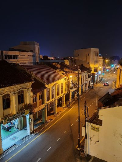 High angle view of illuminated street amidst buildings against sky at night