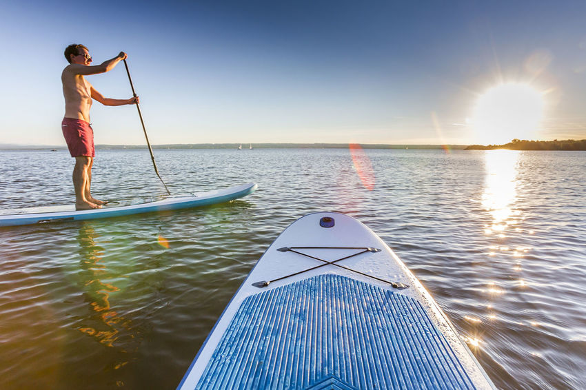 Standup paddler at the lake during sunset Activity Adventure Ammersee Bayern Fitness Holiday Lake Lifestyle Men Nature Nautical Vessel One Person Outdoors Paddleboard Paddleboarding Recreation  Standup Paddleboarding Standuppaddle Sun Sunset Sup Surfer Tour Unfiltered Water