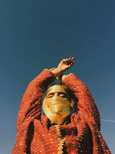 Low angle view of woman face covered with ribbon against blue sky
