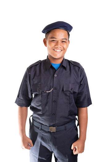 Young Asian man in police uniform isolated on white background. White Background Studio Shot Cut Out One Person Clothing Looking At Camera Standing Young Adult Cap Portrait Men Police Officer Security Face Smile Service Smiling Front View Three Quarter Length Happiness Males  Young Men Occupation Uniform