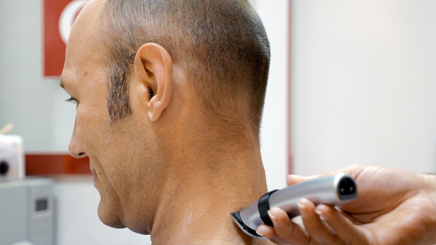 Cropped hand of barber cutting man hair with electric razor