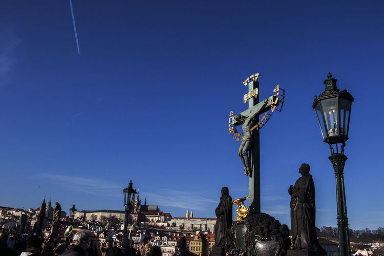 Wide shot of a statue of Christ being crucified on Charles bridge in Prague Sky Architecture Statue Sculpture Clear Sky Blue Human Representation Male Likeness History Outdoors Antique Low Angle View Jesus Christmas Cross Cruxifix Prague Charles Bridge Street Light Religion Christianity Historic Figure Landscape Jesus Statue Jesus Sculpture