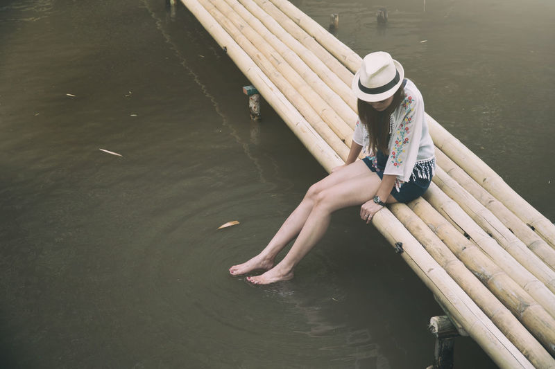 High angle view of young woman relaxing on footbridge over lake