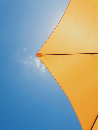 Directly below shot of yellow parasol against blue sky