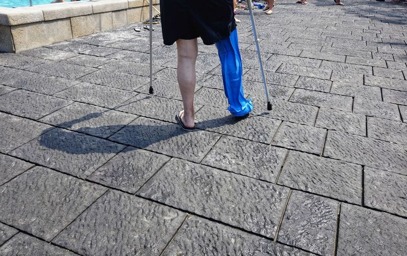 Low section of person with prosthetic leg walking on footpath