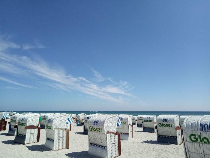 Hooded chairs on beach against blue sky