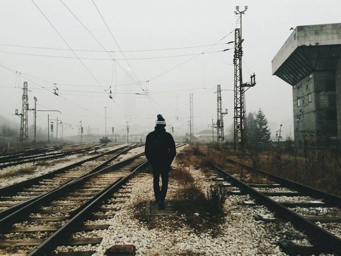 Rear view of man walking on railway tracks