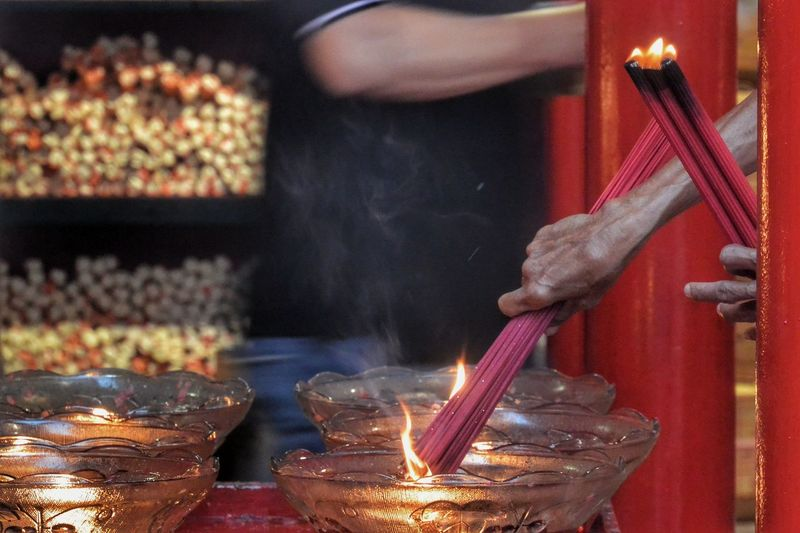 Cropped hands burning incense sticks on temple