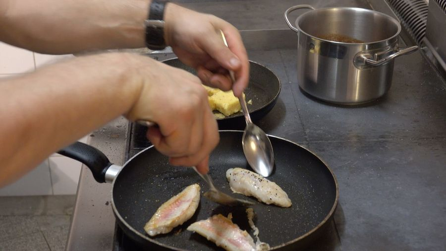 Cropped Image Of Man Frying Fish In Saucepan At Kitchen Counter