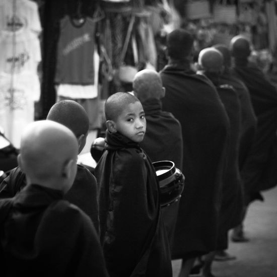 Rear view of monks in queue