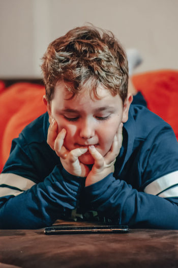 Portrait of boy sitting on mobile  phone at home