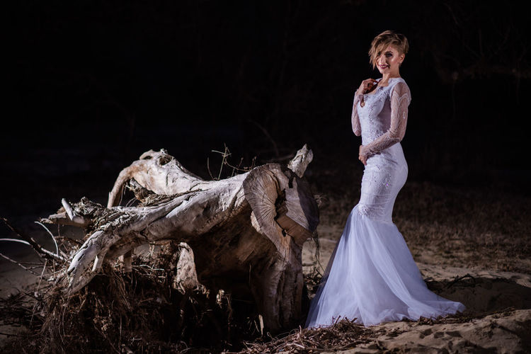 Beautiful woman standing on land at night