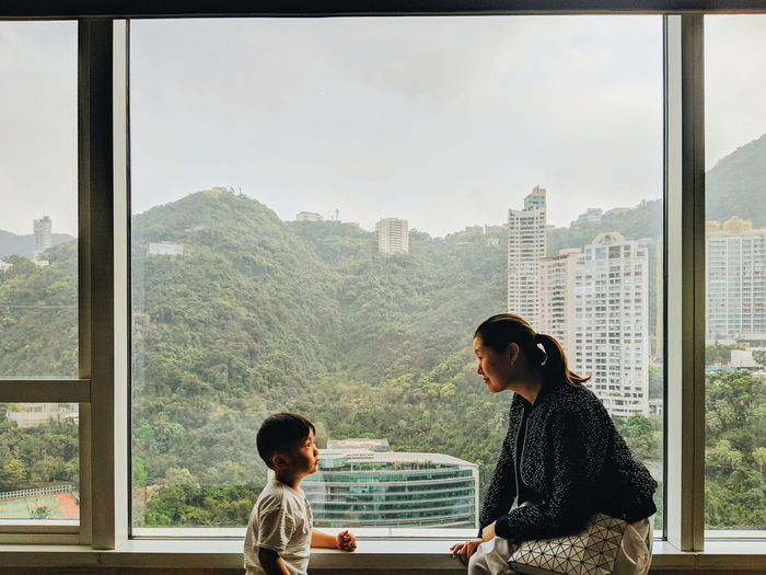 Mother talking with son while sitting on window sill at home