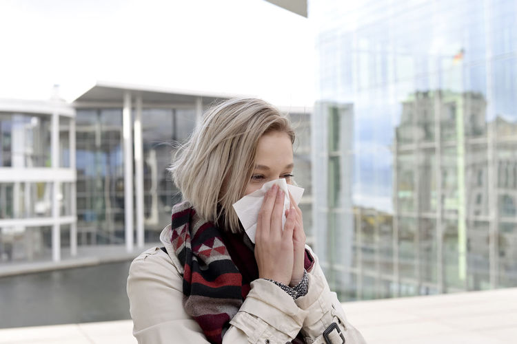 Young woman blowing nose while standing against building