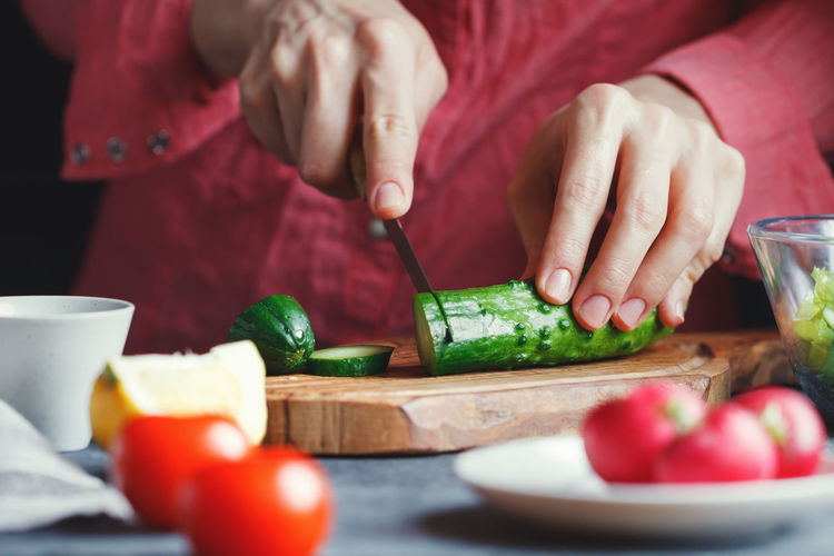 Bowl Chopping Close-up Cutting Cutting Board Day Food Food And Drink Freshness Healthy Eating Holding Human Body Part Human Hand Indoors  Kitchen Knife Lifestyles Men Midsection One Person Preparation  Preparing Food Real People Table Vegetable