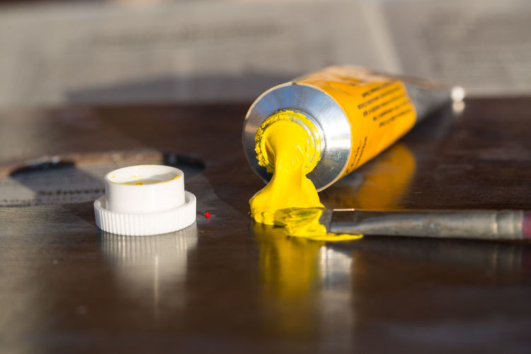 Close-up of yellow paint tube on table
