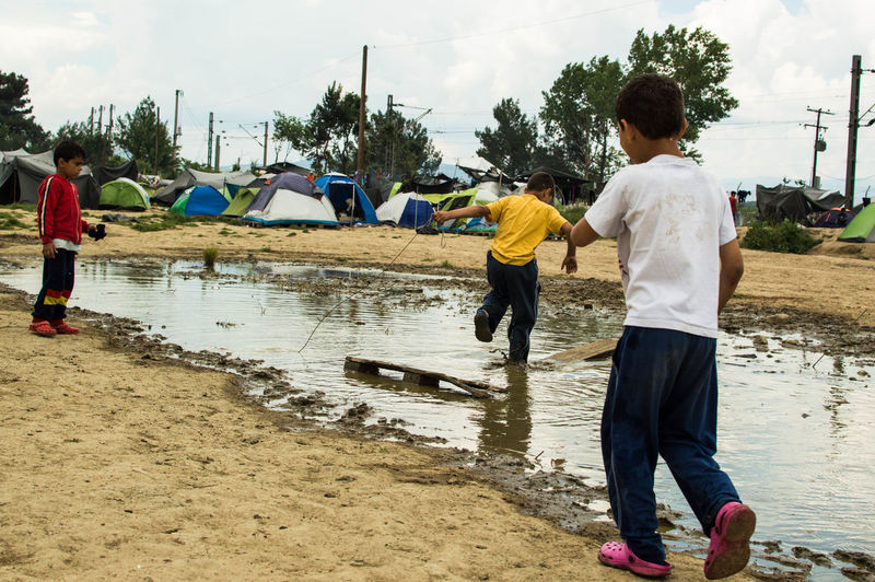 Boys playing in puddle at refugee camp