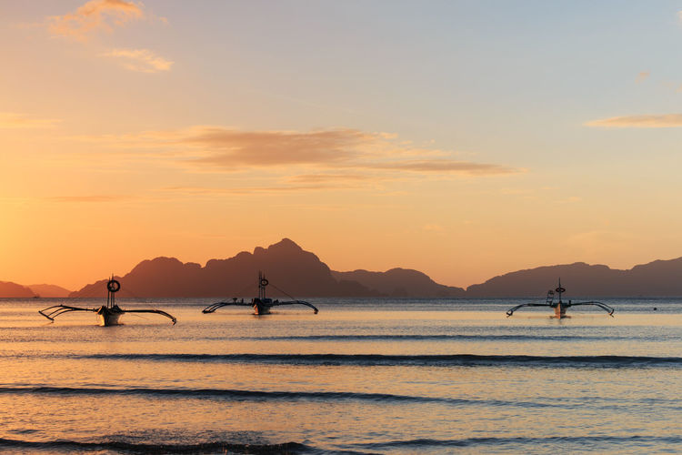 Outrigger boats on sea against sky during sunset