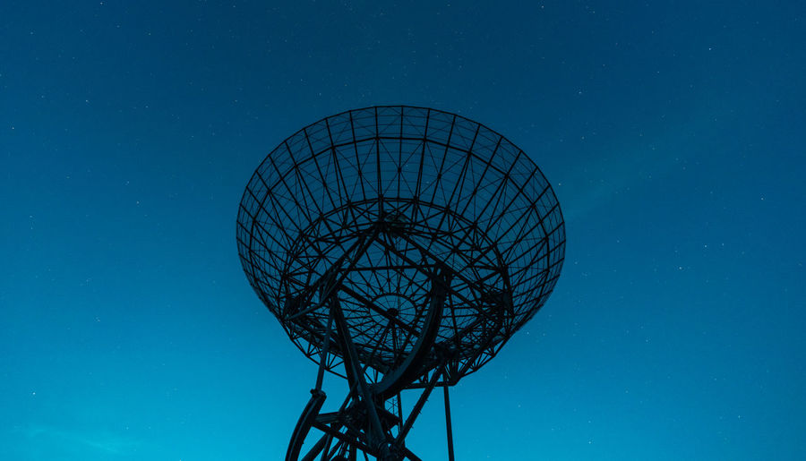 Low angle view of communications tower against blue night sky