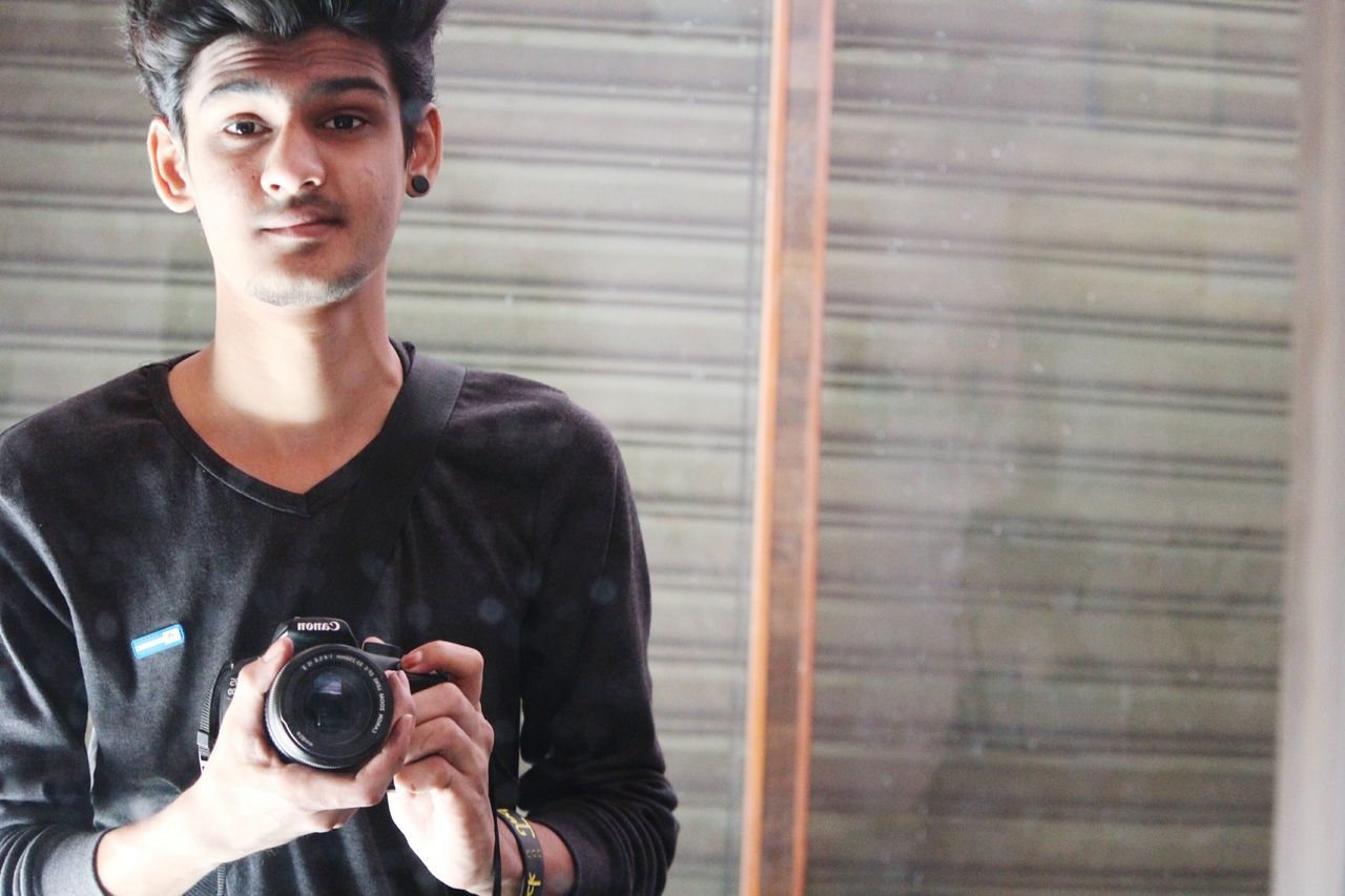 photography themes, camera - photographic equipment, photographer, photographing, looking at camera, portrait, one person, young adult, digital camera, holding, real people, camera, technology, smiling, selfie, outdoors, slr camera, one man only, day, people